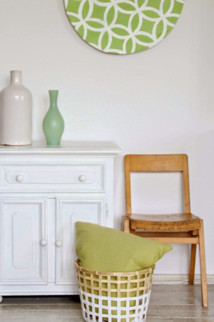 Dekoration einer Kommode mit weißen grünen Vasen und einem Korb mit Kissen darüber hängt grafische Wanddeko