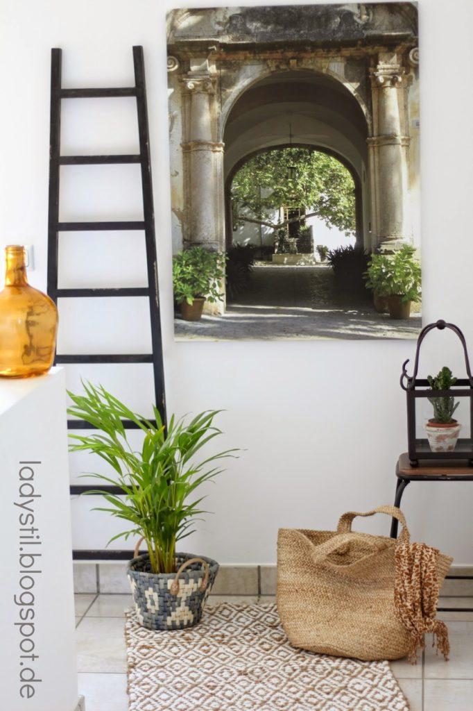 Stilleben einer mit einem Hofeingang bedruckten Leinwand und Leiter, Hocker sowie einem beigen Teppich