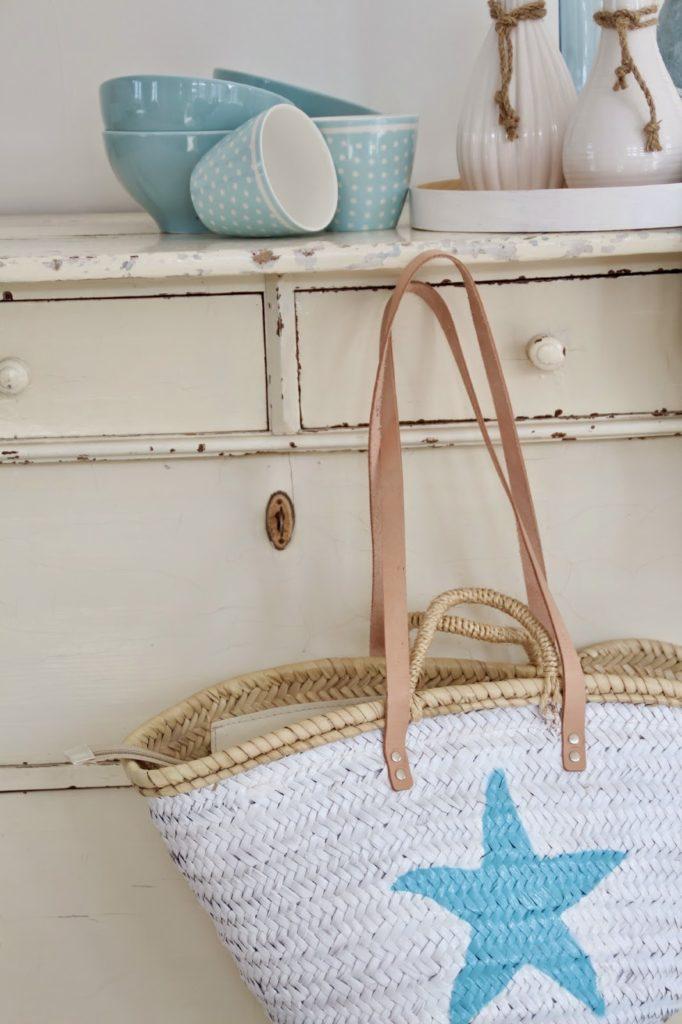 Stilleben hellblauer und weißer Keramik auf einer Kommode davor steht eine Korbtasche in weiß mit hellblauem Seestern