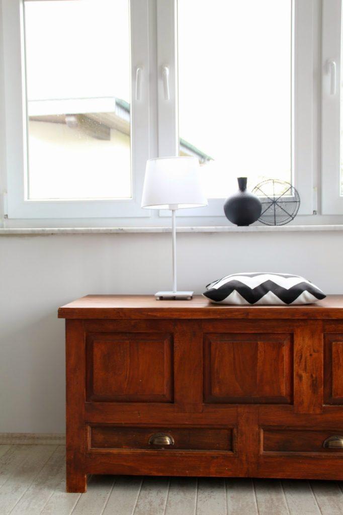 Blick auf eine braune Truhe mit geometrischem Kissen in schwarzweiß und einer weißen Lampe im Hintergrund Fensterbank mit schwarzer Kugelvase