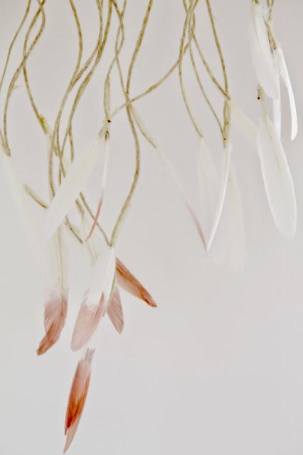Weiße und weißrosafarbene Federn hängen an Kordeln