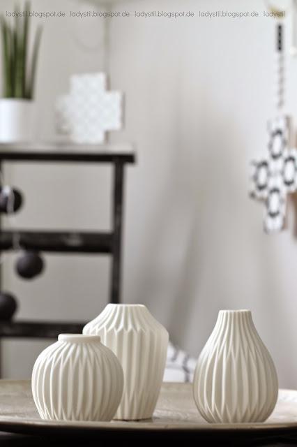 Drei weiße Vasen im Vordergrund im Hintergrund Leiter mit Kreuzen