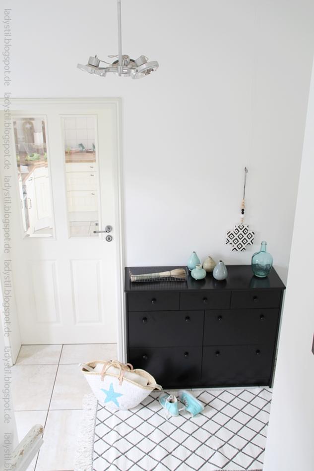 schwarze Kommode mit türkisblauer Deko, Korbtasche und Chucks , Blick auf die Küchentür