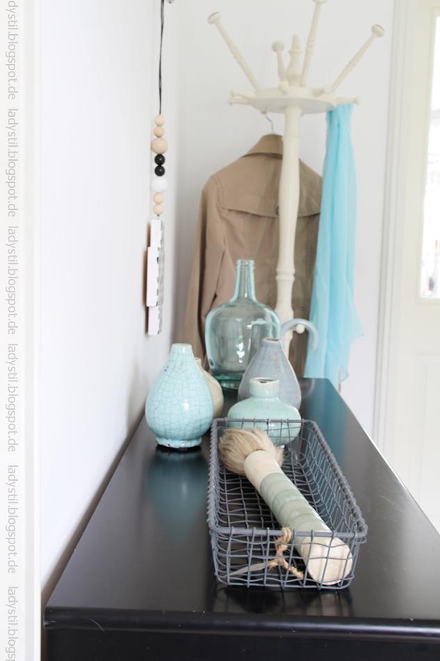 schwarze Kommode mit türkisblauer Deko und Garderobe im Hintergrund