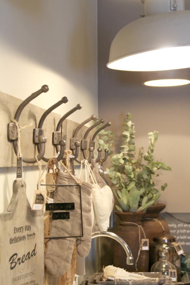 Hakenleiste in der Küche mit Schneidbrettern und Küchentüchern in beige schwarz dekoriert