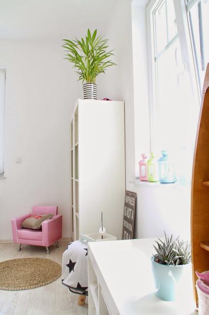 Ansicht einer Zimmerecke mit Bücherregal pinkem Sessel Segelboot alles im Beach-Style