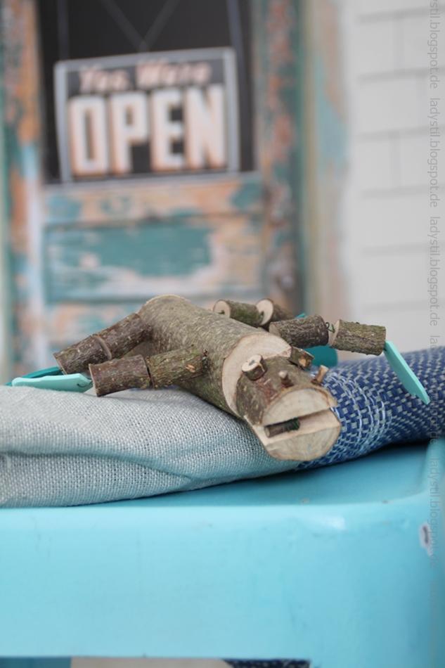 Türkiser Hocker, auf dem ein DIY-Krokodil aus Holzstücken liegt