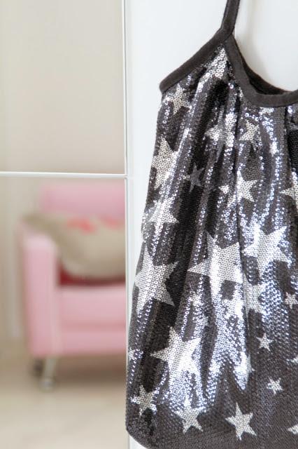 Blick in den Spiegel zeigt den pinken Sessel am Schrank hängt eine schwarze Tasche mit silbernen Sternen
