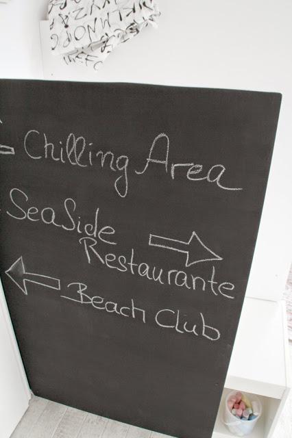 """Schwarzes Brett mit Tafellack beschriftet mit weißer Kreide """"Chilling Area"""" """"Seaside Restaurant"""""""