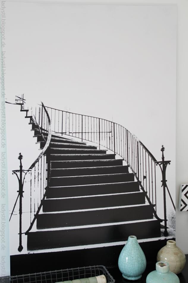 Poster einer schwarzen Wendeltreppe auf weißem Grund hängt über einer schwarzen Kommode