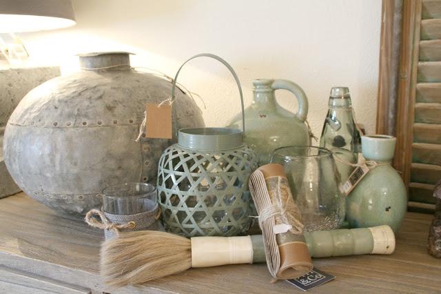 grüne Wohndeko mit kleinen Vasen und Laterne aus grünem Bast