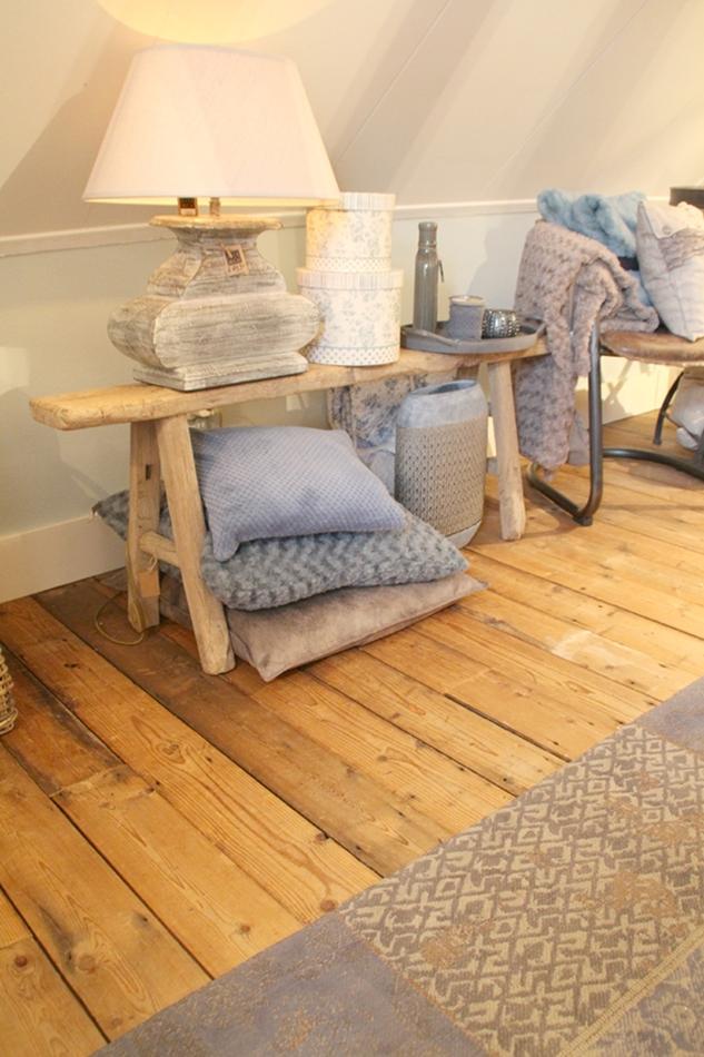 Ansicht einer kleinen Holzbank mit diversen Dekoaccessoires darauf, Kissen, Vasen, Schachteln in beige blau grau