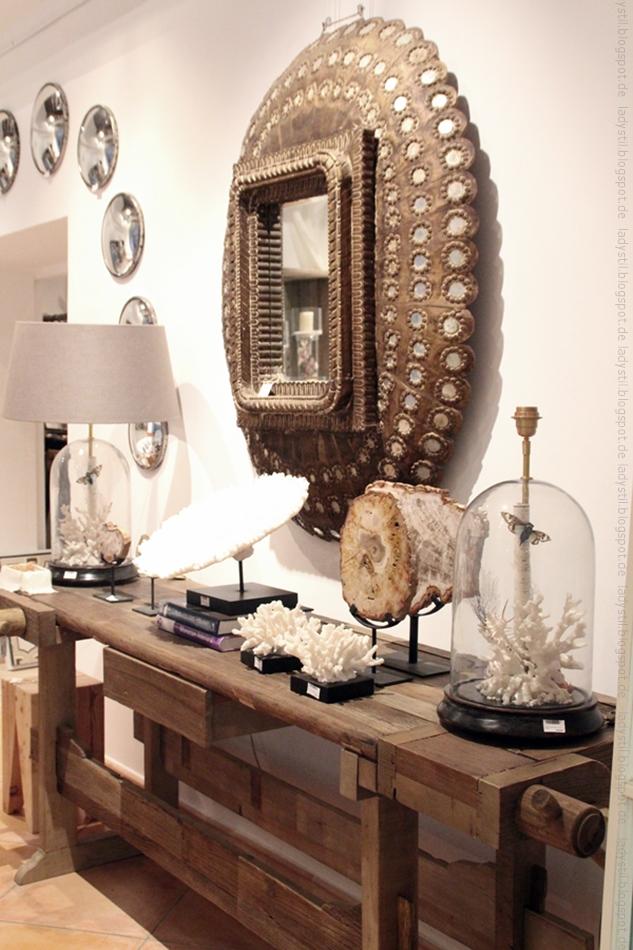 Holzkommode mit diversen Wohnaccessoires und einem riesigen runden Spiegel darüber im Geschäft Bondian Living in Palma