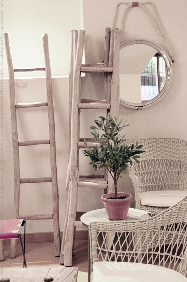 Stor Bondian Living in Palma Blick auf drei Leitern mit Sitzgruppe aus Bast und einem rundem Spiegel