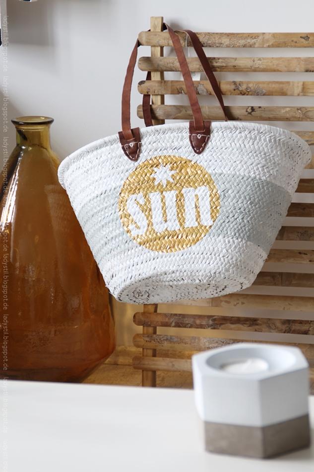 Korbtasche weiß mit goldenem Kreis und weißem sun Schriftzug darin hängt an einer Bambuspinnwand daneben eine große braune Bodenvase für den Bloggeroptimierungsfotowettbewerbbeipixum