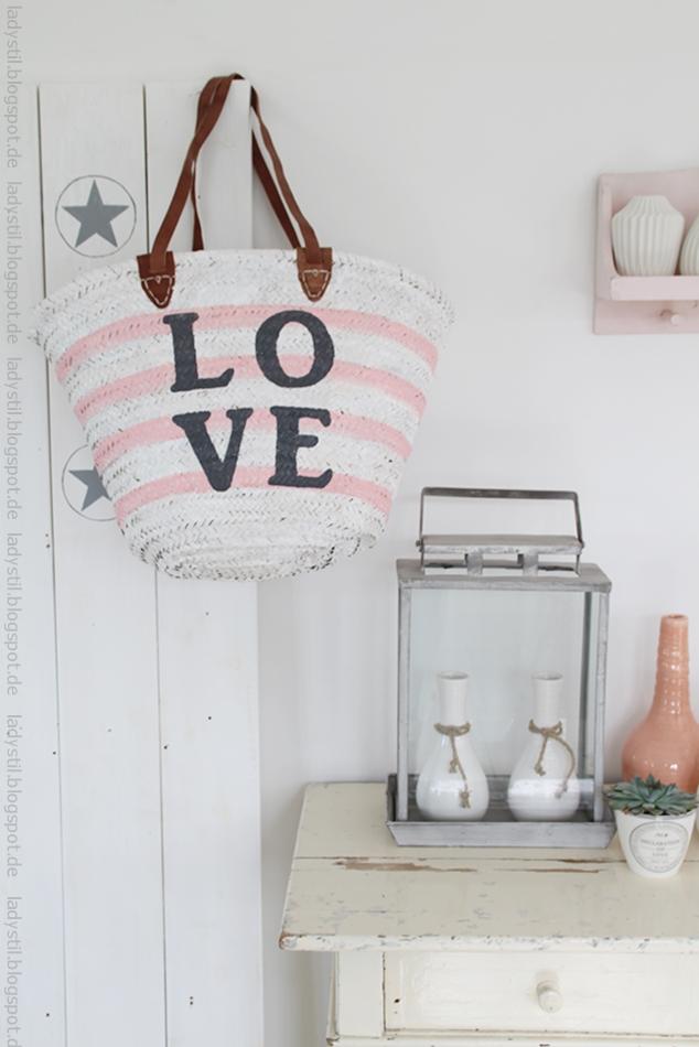 Weiß rosa gestreifte Korbtasche mit großem love Schriftzug hängt an einer Sternentafel rechts davon Kommode mit diversen Wohnaccessoires für den Bloggeroptimierungsfotowettbewerbbeipixum