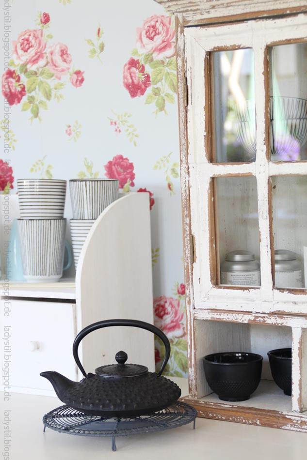 Teekanne-in-schwarz-mit-vintage-regal-im-hintergrund-und-schwarzweiß-gestreiften-Bechern-von-house-doctor