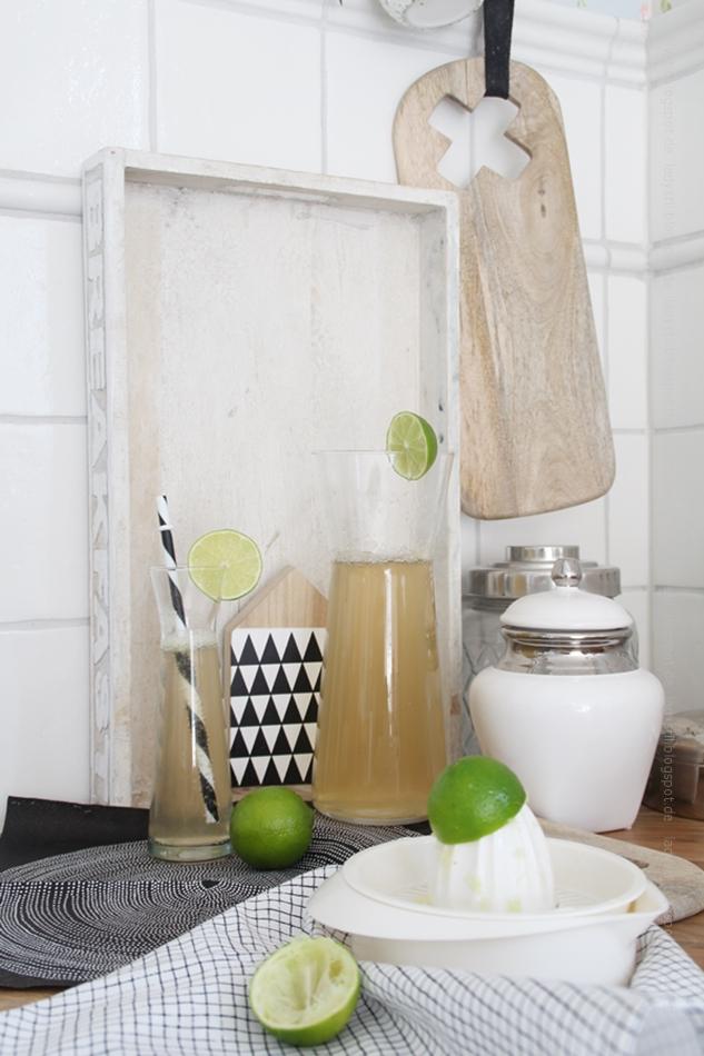 Hugo im Glas mit Strohhalm und Limette sowie Deko drumherum in schwarz weiß grün