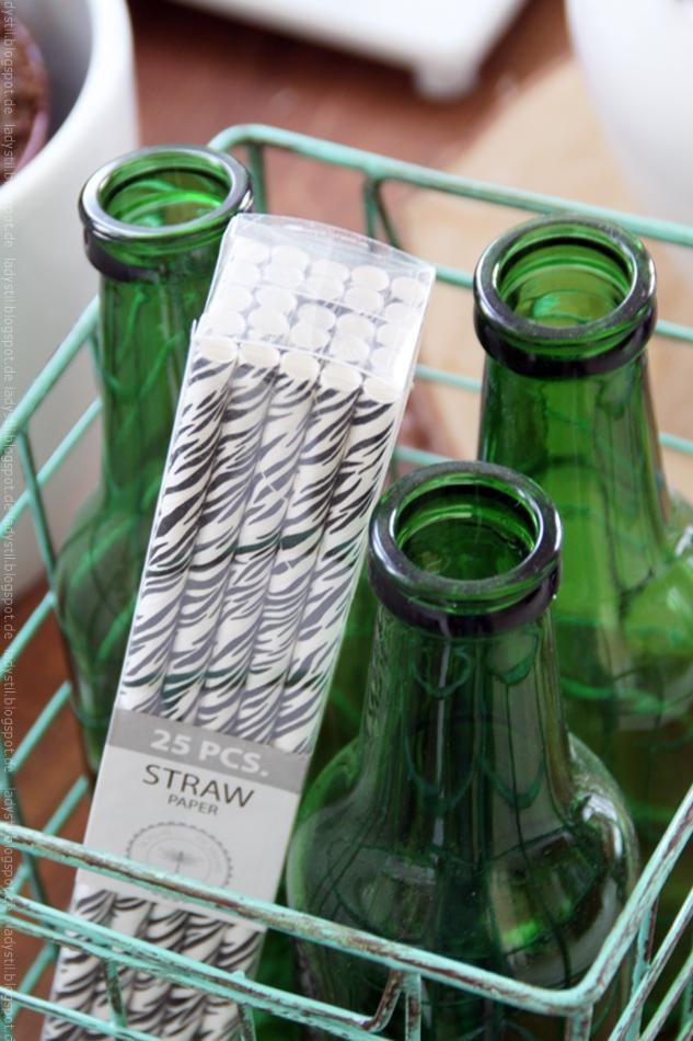 Drei grüne Flaschen im Korb mit Strohhalmen Zebra black white