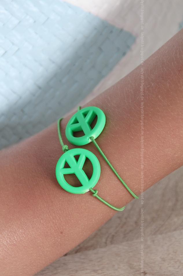grünes Peace-Armband am Arm