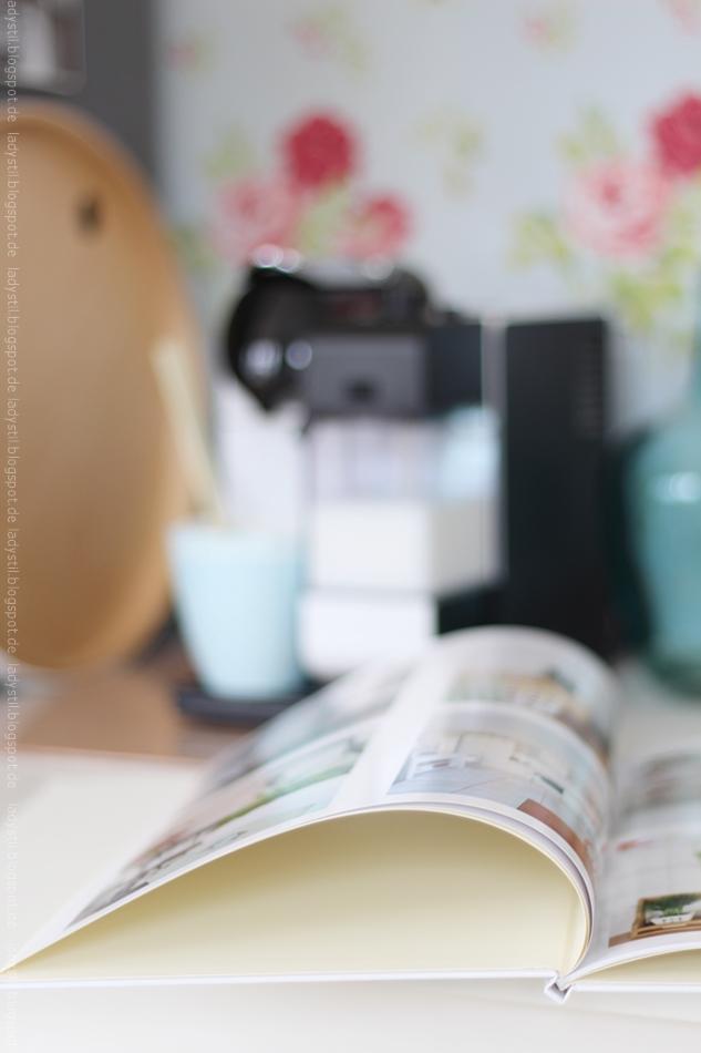 Blick auf ein Fotobuch im Hintergrund verschwommen die Kaffeemaschine
