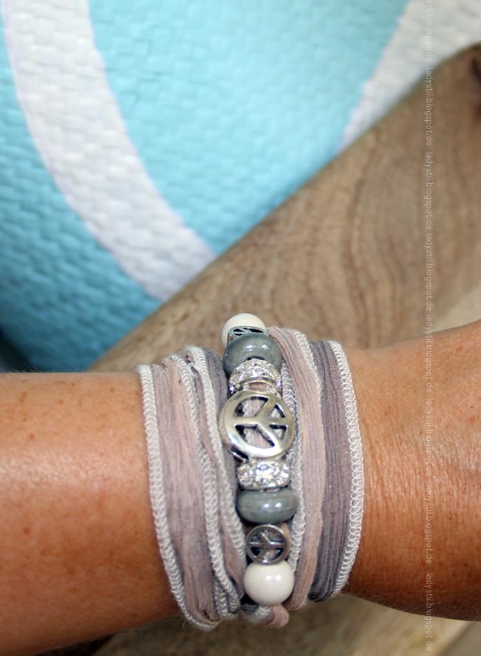 fertiges Armband Seidenband mit Charms unter anderem Peacezeichen am Arm