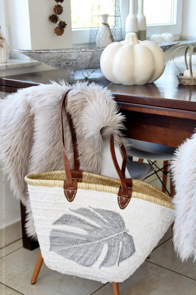 Korbtasche mit Monsgterablattbemalung hängt an einem Stuhl vor einem Tisch mit Herbstdekoration