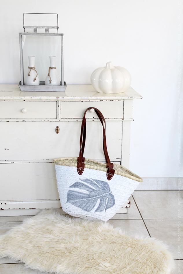 Korbtasche in weiß mit grauem Monsterablatt bemalt vor einer beigen Kommode mit Kürbisdekoration