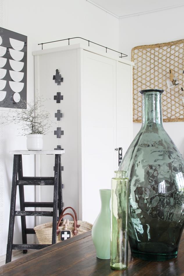 grüne Vasen auf Kommode vor einem weißen Schrank mit schwarzweiß Bild im grafischen Stil
