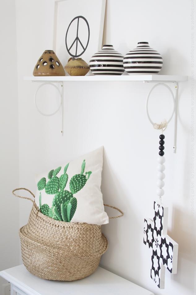 Kissen mit Kakteendruck in einem Korb unter einem Regal mit schwarzweißen Vasen