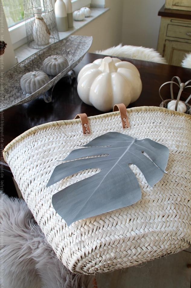 Schablone eines Monsterablattes liegt auf einer weißen Korbtasche