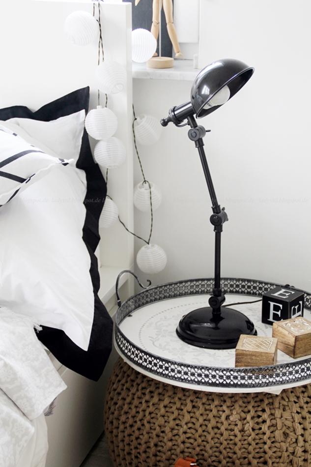 Interior Schlafzimmer in weiß schwarz Holz mit Pouf als Nachttisch und Industrialstyle Lampe