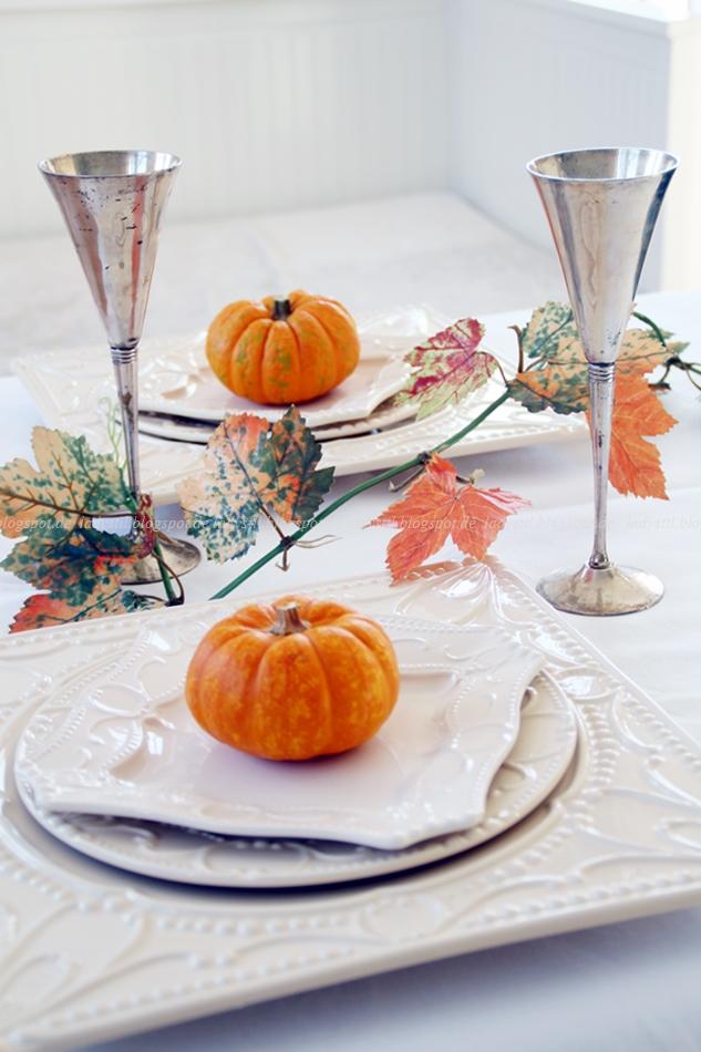 Beige herbstliche Tischdeko mit Kürbisdekoration in orange und silbernen Trinkbechern