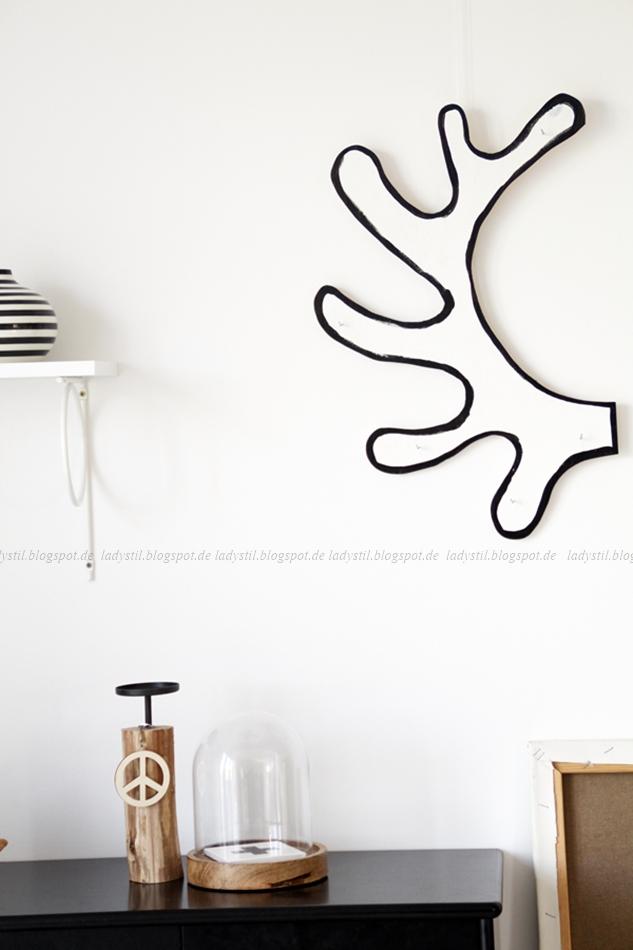 Geweih aus Holz ausgesägt und angemalt hängt über einer schwarzen Kommode