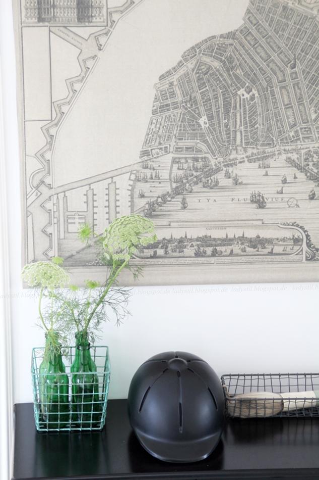 schwarze Kommode mit grünen Blumen, daneben ein Reiterhelm, darüber eine Wandkarte aus Amsterdam