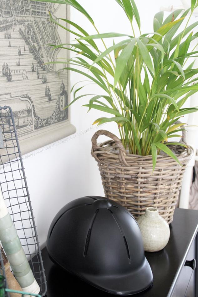 Flur mit schwarzer Kommode darauf ein Reiterhelm und Plants Urban Jungle