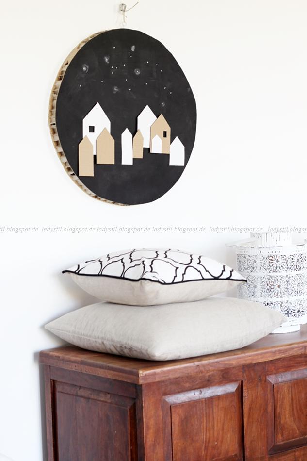Truhe mit Kissen und rundes weihnachtliches DIY Upcycling Wandbild mit Häusern aus Pappe und Papier