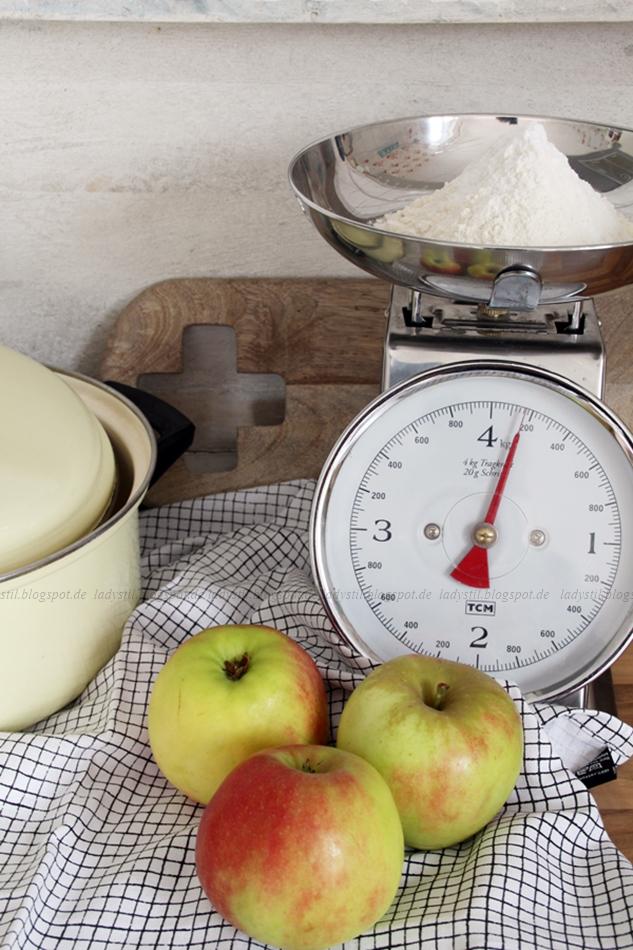 Zutaten Apfelkuchen, Äpfel vor einer mit Mehl befüllten Waage