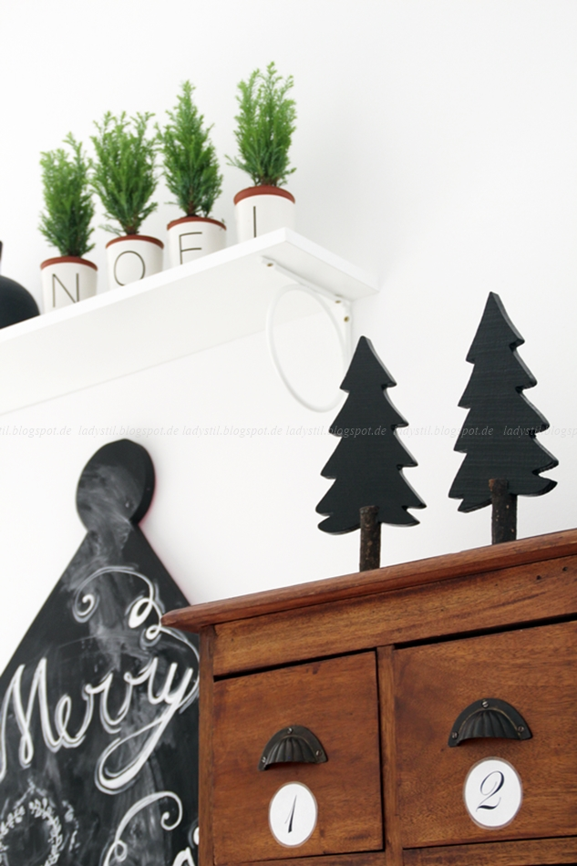 """Blick auf eine antike Apothekerkommode mit schwarzen Weihnachtsbäumen und vier Koniferen in Übertöpfen die das Wort """"Noel"""" bilden, DIY Lichthäuser"""