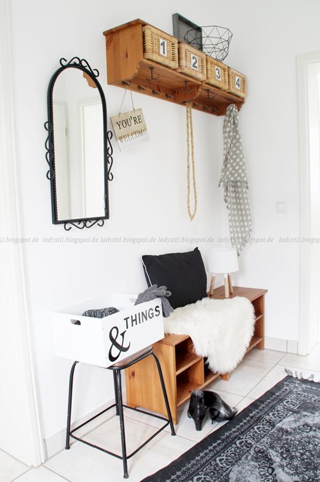 Blick in den Flur mit Garderobe Spiegel und Wohnaccessoires in schwarz weiß Holz als Kombination