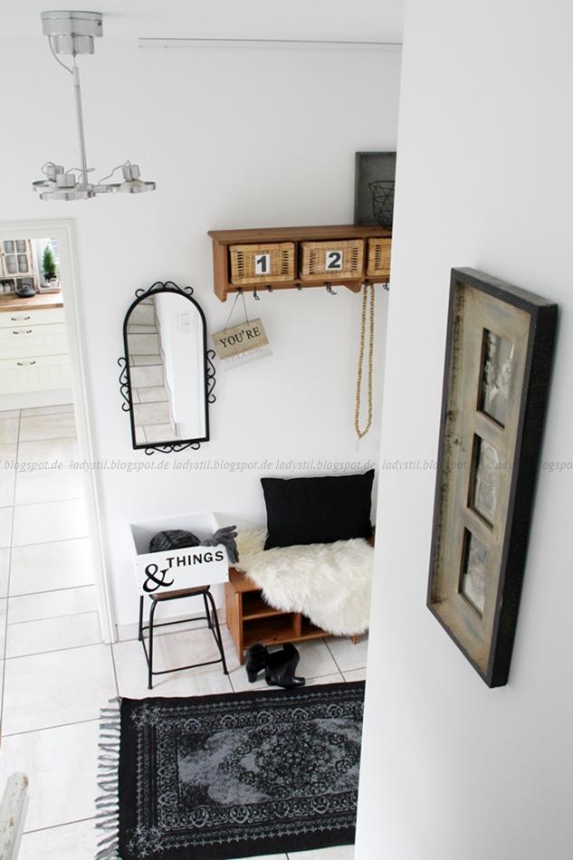 Blick auf eine Garderobe im Flur Styling mit Holz schwarz weiß
