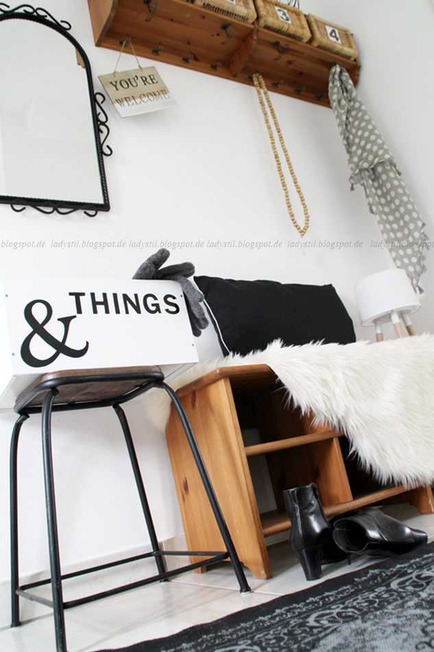 Entry Styling mit Garderobe und Blick auf die Sitzbank aus Holz mit schwarz weißen Accessoires