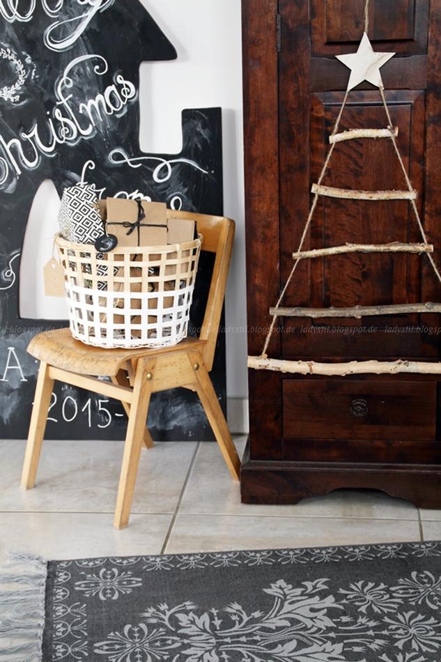 DIY Weihnachtsbaum aus Ästen hängt an einem Schrank