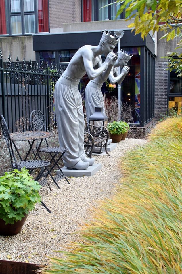 Garten des Hotels Andaz Hyatt Amsterdam mit zwei Skulpturen an einem Kiesweg