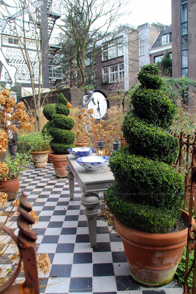 Garten des Hotels Andaz Hyatt Amsterdam mit Mosaikweg und Buchsbaumsäulen sowie dekorativen Elementen