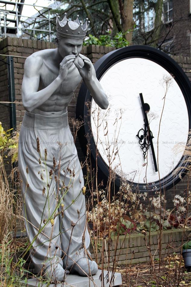 Garten des Hotels Andaz Hyatt Amsterdam mit großer Skulptur und Uhr im Hintergrund