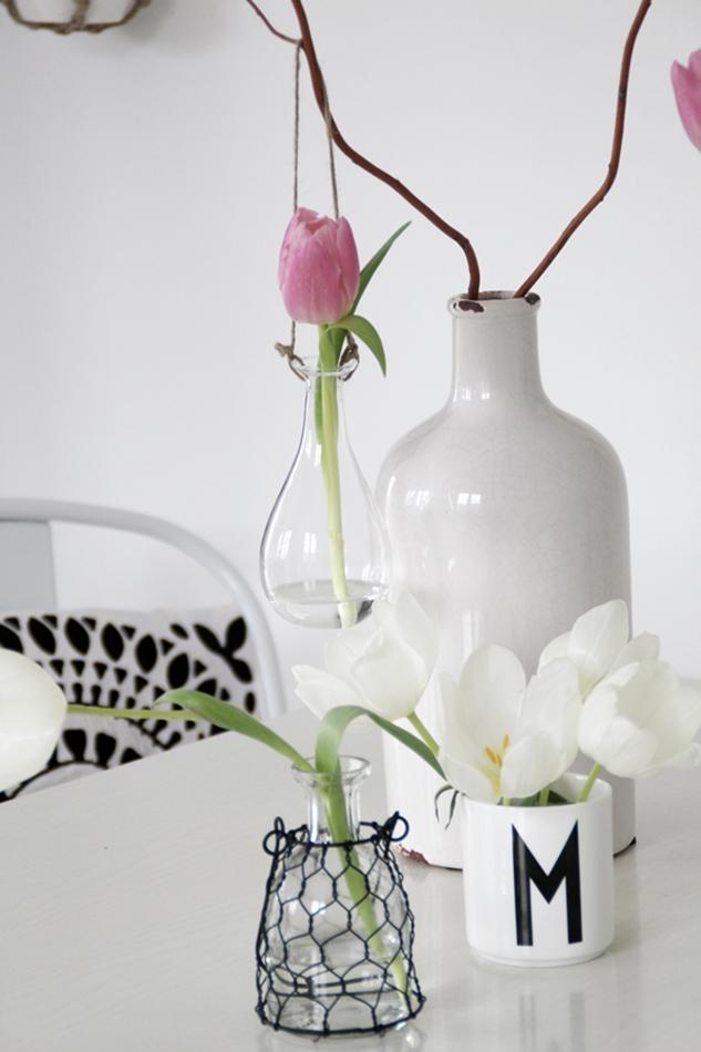 Glasvasen zum Aufhängen mit Sammelsurium an Gefäßen und Tulpen