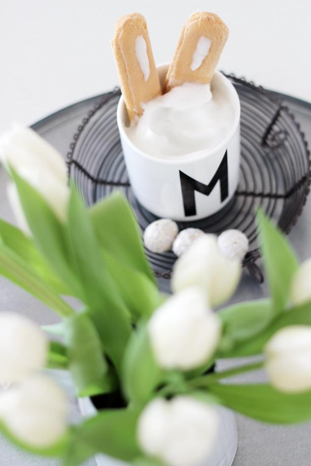 Design Letters Tasse mit Löffelbiskuits als Hasenohren, daneben stehen weiße Tulpen