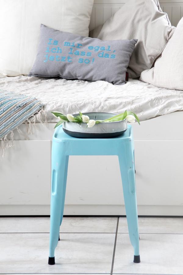 Blick auf das Tagesbett mit einem türkisen Hocker davor worauf eine Schale mit liegenden Tulpen steht