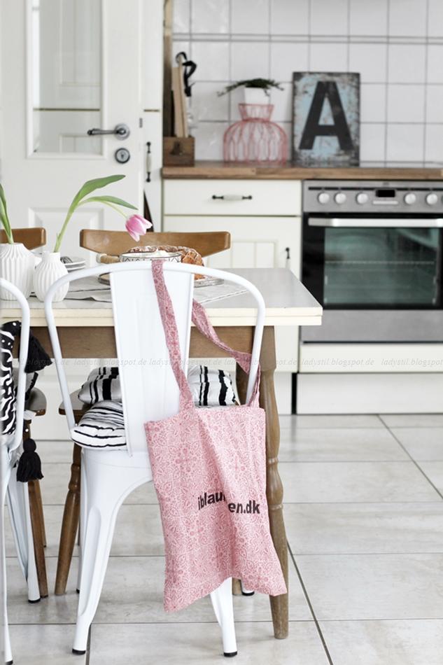 Mit leichten Pastellfarben zieht der Frühling in die Küche ein! Küchenumstyling mit neuen Gelenk-Lampen! BLick über den Tisch hinweg zur Küchenzeile mit rosa Accessoires